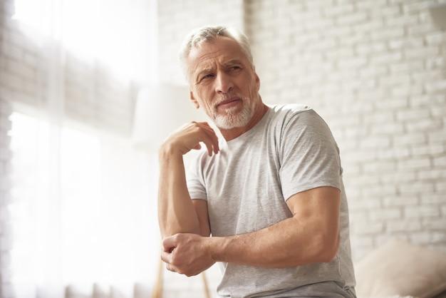 変形性関節症の肘の痛みに苦しんでいる老人。