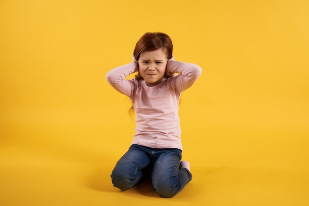 小さな女の子は耳を覆っています。とてもうるさい。
