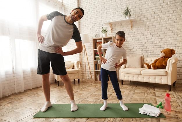 Отец и дочь делают упражнения на растяжку в домашних условиях.