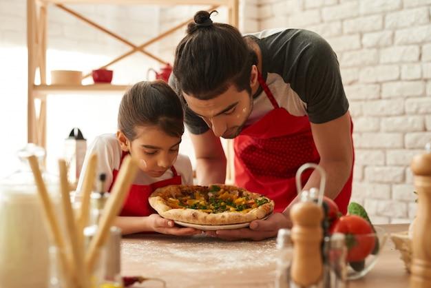 男と女は、キッチンで美しいピザを調理しました。