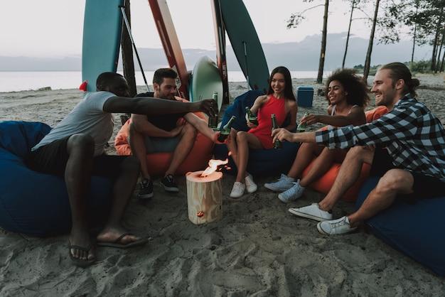 人々は燃えるログの周りのビーチで休んでいます。