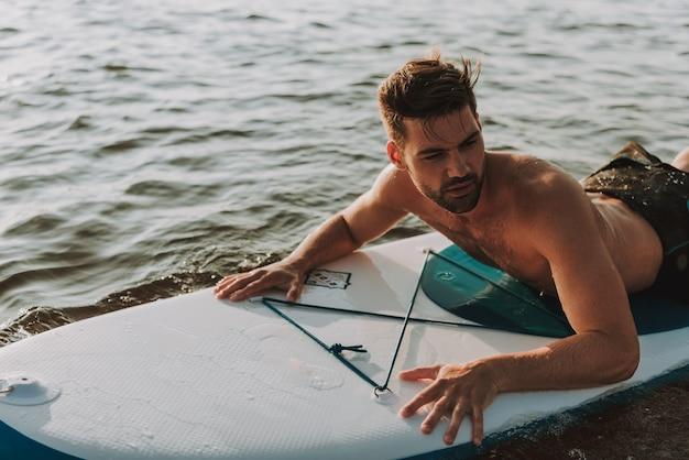 若い男は水で泳ぎ、泳ぐ。