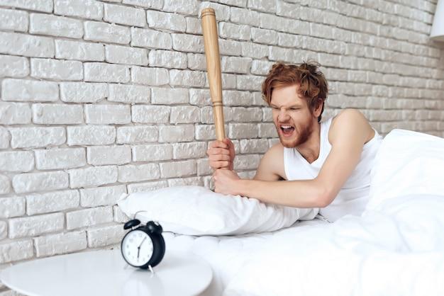 男は目覚まし時計で野球のバットを振った