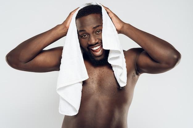 アフリカ系アメリカ人の男がタオルで頭を拭きます。