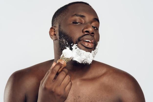 アフリカ系アメリカ人の男は、シェービングクリームを塗ります。