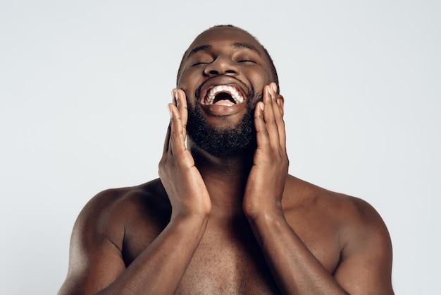 アフリカ系アメリカ人の笑みを浮かべて男はフェイスクリームで塗られています。