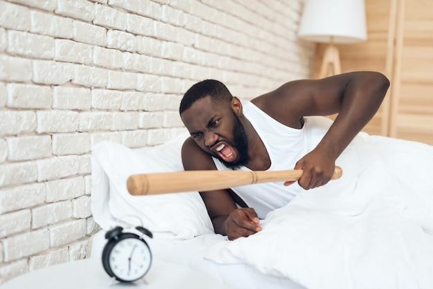 アフリカ系アメリカ人の怒っている男は野球のバットを脅かす