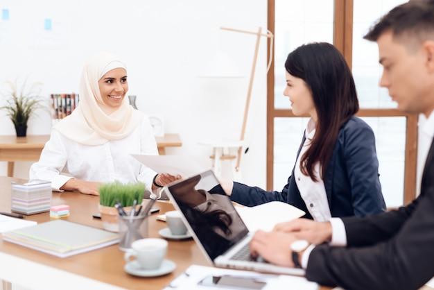 Арабка в хиджабе вместе работает в офисе.