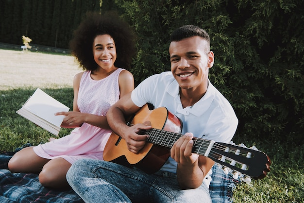 男は彼の女の子にギターを弾いています女性は本を読んでいます