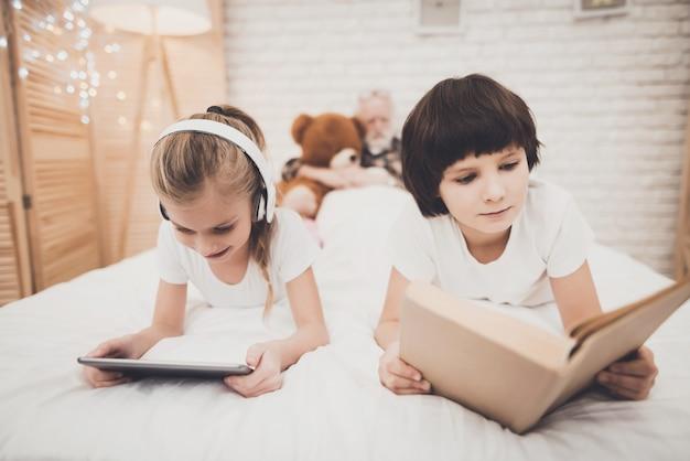 Дети читают книгу на кровати