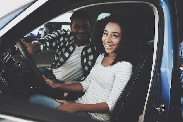 Счастливая пара, улыбаясь, сидя в машине