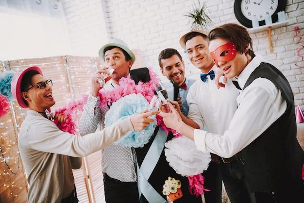 Веселые парни чокаются бокалами шампанского на вечеринке.
