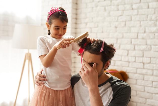 子供は白いレンガの父親の髪を編んでいます。