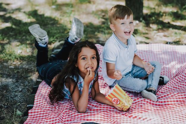 小さな子供たちは公園の家族のピクニックでポップコーンを持っています