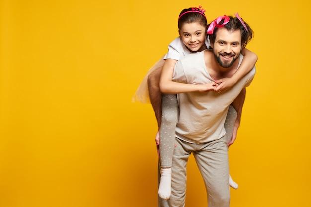 Счастливая маленькая улыбающаяся девочка едет на спине отцов