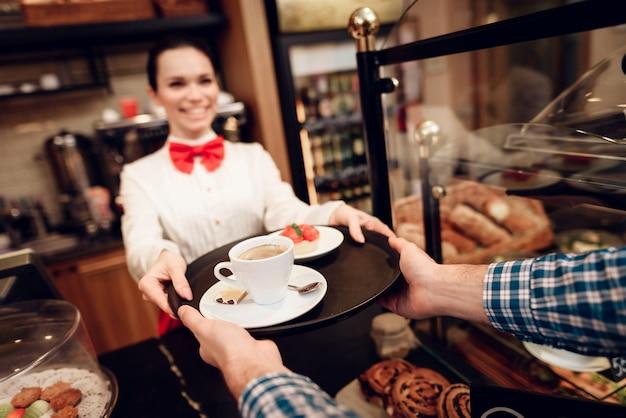 男にケーキと一杯のコーヒーを与える笑顔の女の子