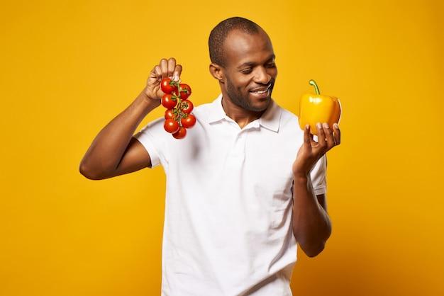 男はトマトと黄色のピーマンの束を保持します。