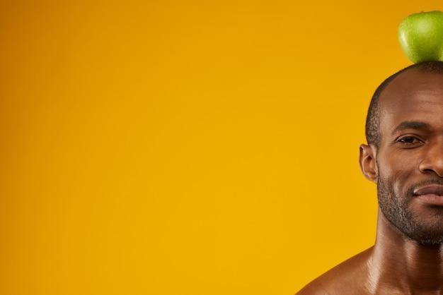 幸せなアフリカ系アメリカ人の男は頭の上にリンゴを保持しています。