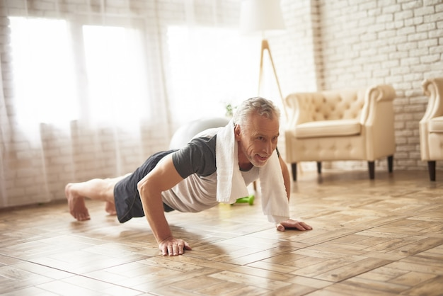 Планка статические упражнения улыбающийся пожилой мужчина спорт.