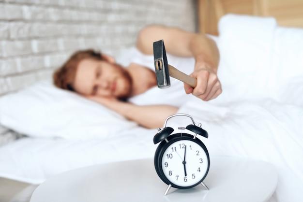 若い赤髪の男は目覚まし時計をハンマーします。睡眠不足。