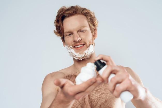 若い赤髪の男は、シェービングクリームを適用します。