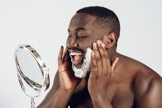 アフリカ系アメリカ人の男が顔にシェービングクリームを塗ります