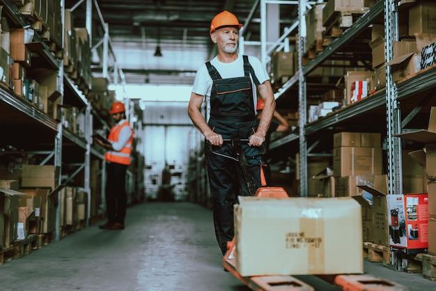 フォークリフトカートを使用してヘルメットの倉庫の男