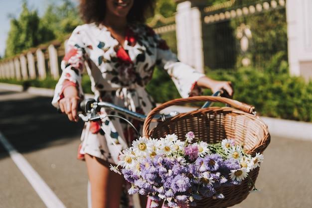 美しいドレスを着たムラートが外をサイクリングしています。