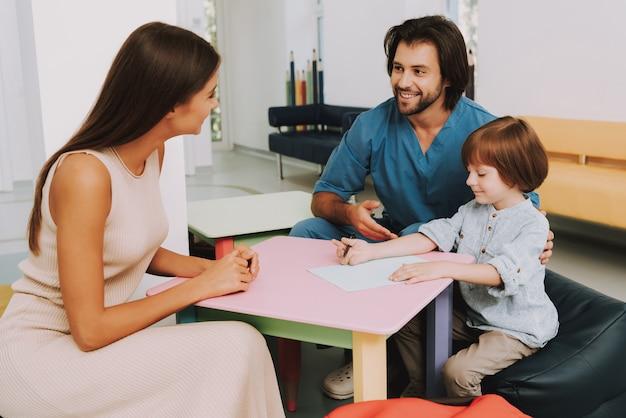 Малыш рисует в офисе педиатра для снятия стресса.