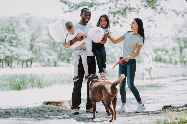 Папа и дети играют в парке счастливая семья и собака.