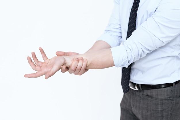 Человек в костюме держит больную руку на белом фоне.