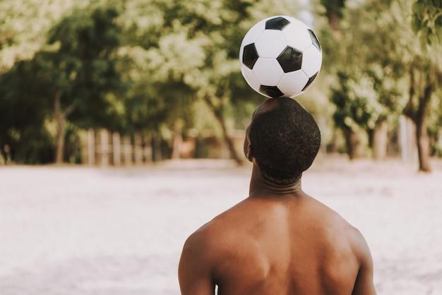 ビーチでスポーツマンは頭の上にサッカーボールを保持します。