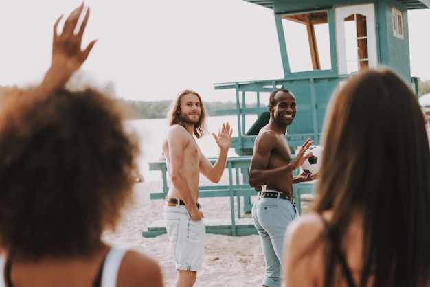 流行に敏感な男性がビーチでサッカーの試合を離れる