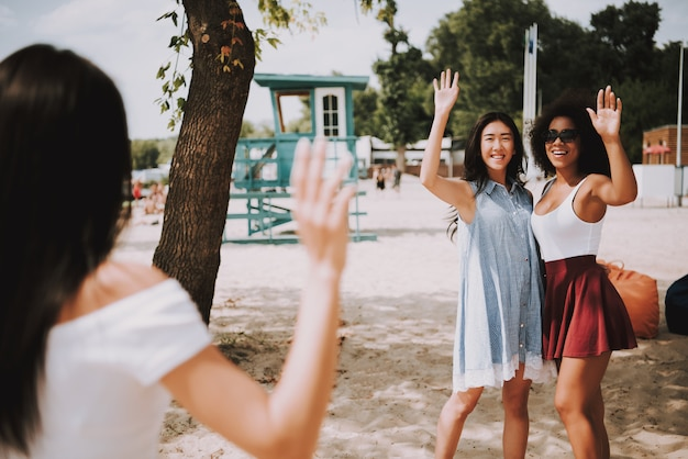 多民族の友人たちの女の子が夏の海岸で会います