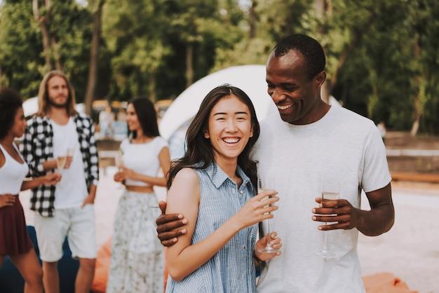 アフリカ人アジア人の女の子がビーチパーティーで飲みます。