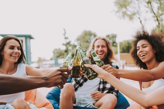 Молодые люди приветствуют пивные бутылки на солнечном берегу.