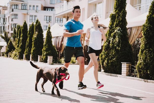 カップルは大きな犬と一緒に道路を走っています。