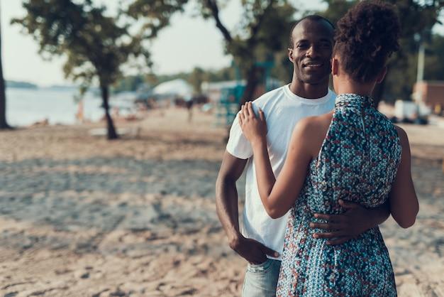 アフリカ系アメリカ人カップルはビーチで休んでいます。
