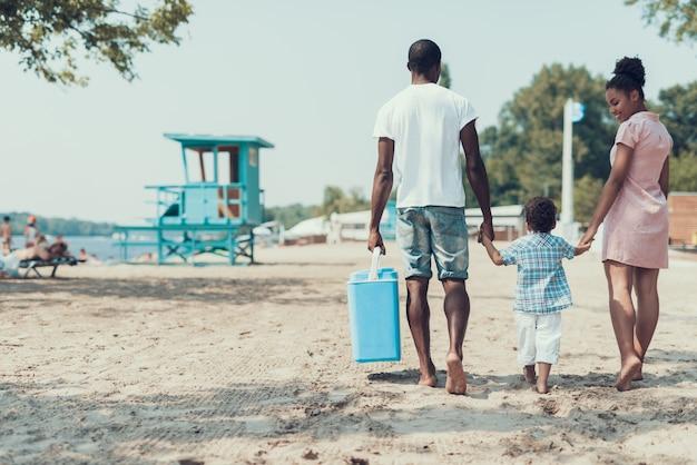 アフリカ系アメリカ人の家族は砂浜を歩いています。