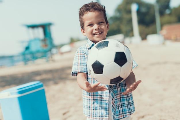 アフリカ系アメリカ人の少年はビーチで休んでいます。