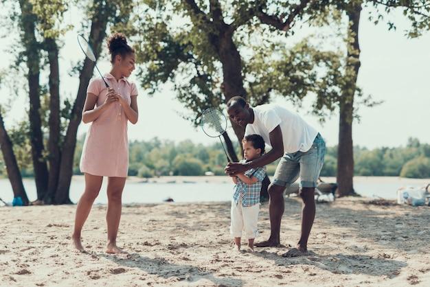 Афроамериканская семья играет в теннис на песчаном берегу