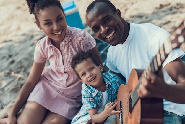 アフリカ系アメリカ人の家族はビーチで休んでいます。