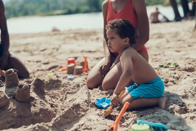 アフリカ系アメリカ人の家族は砂浜で休んでいます。