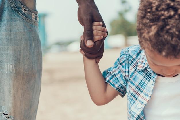 アフリカ系アメリカ人の父と息子のクローズアップは手をつないで