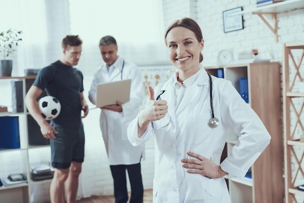 医者はクリニックでフットボール選手に話しています。