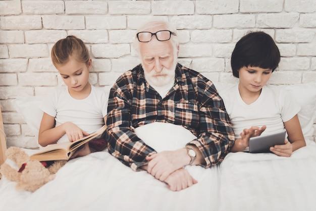 おじいちゃんが眠る子供たちがタブレットで遊ぶ本を読んでベッド