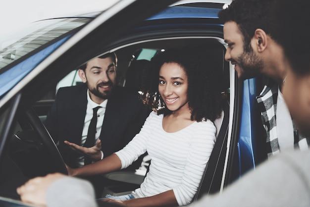 若いアフロ家族はディーラーで母のために車を買う
