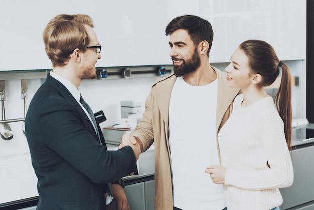 Продавец в костюме и клиент с женой пожимают друг другу руки