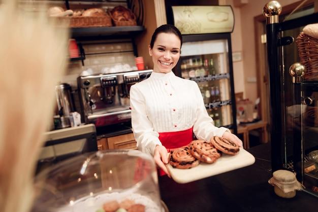 パン屋さんでロールと立っている若い笑顔の女性