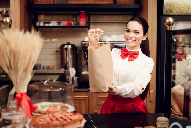 パッケージのパンと一緒に立っている若い笑顔の女性
